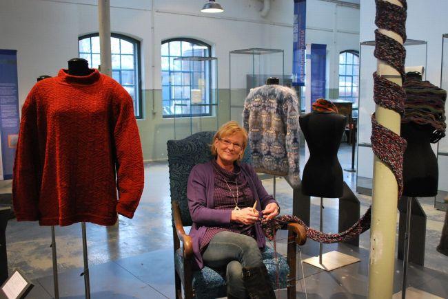 Eine Mitarbeiterin des Museums strickt am Ausstellungsschal
